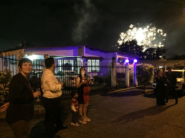 People in a street in front of a house, watching fireworks