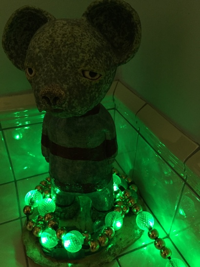 A sad mouse statue ringed with green lights