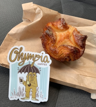 "A kouign amann pastry and a sticker ""Olympia coffee"""